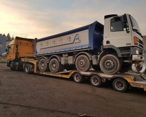 Un grande carro attrezzi trasporta un camion cassonato
