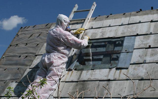 un uomo con una tuta protettiva su una scala al lavoro su un tetto in amianto