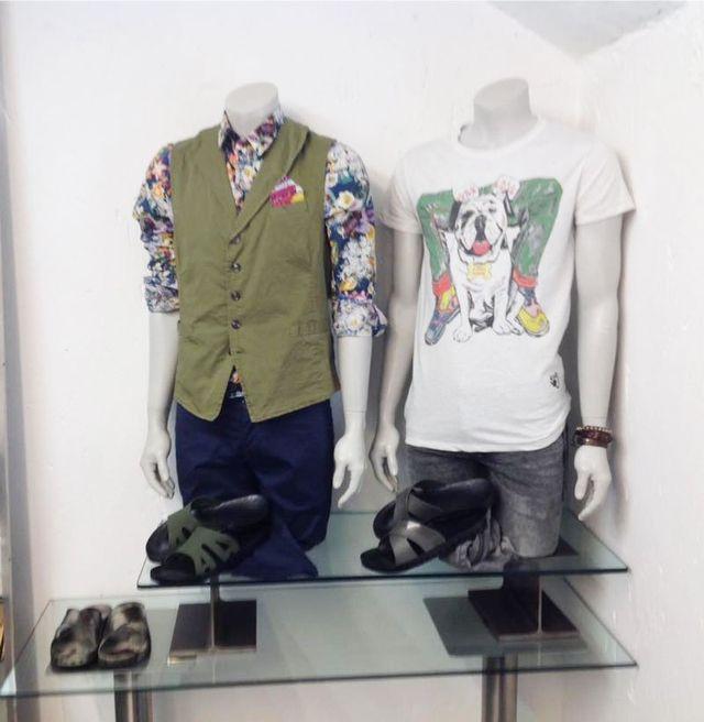 una camicia a fiori, un golf verde con colletto a v e una maglietta bianca con disegnato un cane bulldog appesi su due manichini