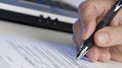 mano di una persona mentre scrive su un foglio con penna