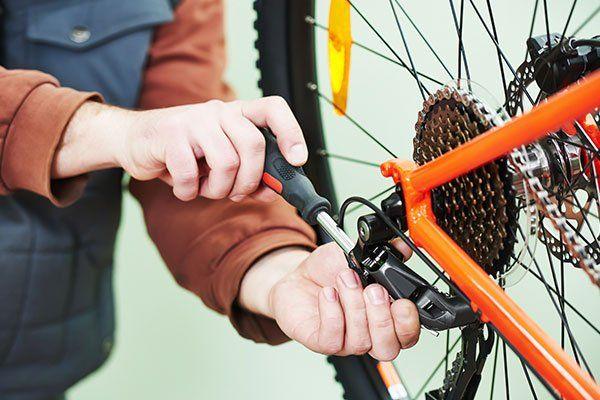 due mani che riparano una bicicletta arancione