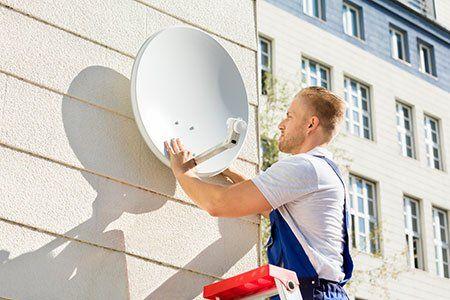 un lavoratore mentre installa un'antenna parabolica