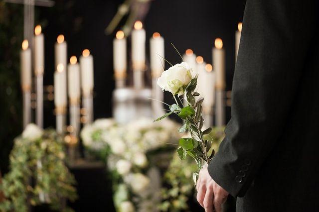 la mano di un uomo con una rosa bianca e davanti delle candele accese