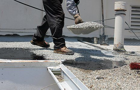 Workers use tar, gravel on a flat roof