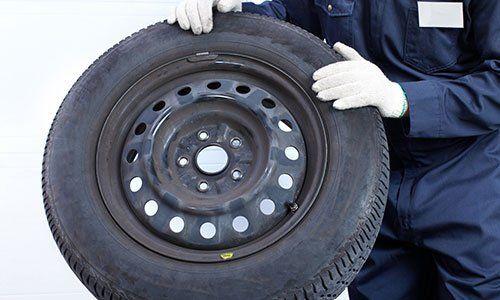 un gommista che tiene in mano una ruota con un pneumatico