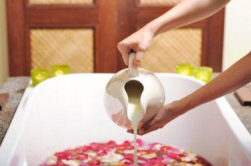 mani di donna che  versano latte in un vasca da bagno