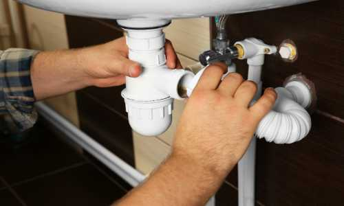 un idraulico che assembla due tubi di un lavandino