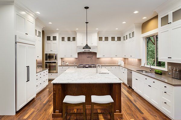 Grande Interni cucina con isola, Lavandino, armadi bianchi, luci del pendente, e pavimenti in legno in nuova casa di lusso