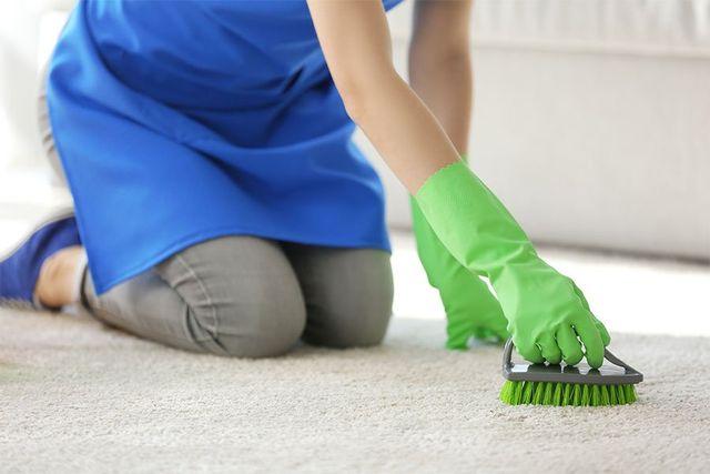 donna che spazzola un tappeto