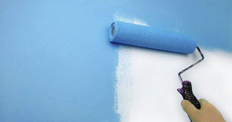 painting a wall blue using a roller