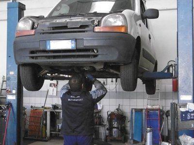 Meccanico al lavoro su un furgoncino sopraelevato