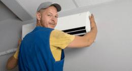 addetto mentre monta un impianto di aria condizionata