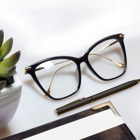 occhiali da vista con montatura nera poggiati su un tavolo accanto a pianta