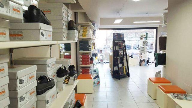 interno di un negozio con sulla sinistra uno scaffale bianco con delle scatole di scarpe e alcuni sgabelli quadrati di pelle arancione