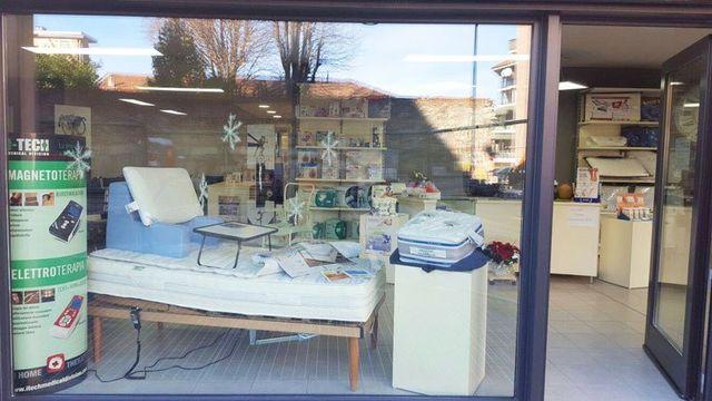vetrina del negozio vista da fuori con sulla sinistra un rilievo di cartone di color verde che sponsorizza la magneto terapia e l'elettro terapia e accanto un letto singolo di legno con sopra un materasso
