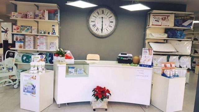 vista del bancone all'interno del negozio con davanti per terra un vaso con una stella di Natale, dietro su entrambi i lati degli scaffali con dei prodotti in scatola e al centro un grande orologio da muro rotondo di color grigio