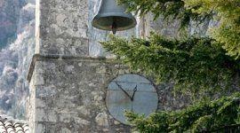 un orologio, un albero e le campane di una chiesa