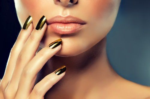 Un donna con unghie di colore verde metallico si sfiora il viso e le labbra