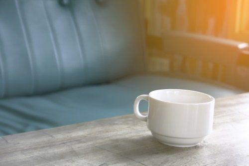 Tazza di caffè sulla tavola con un divano verde in sfondo
