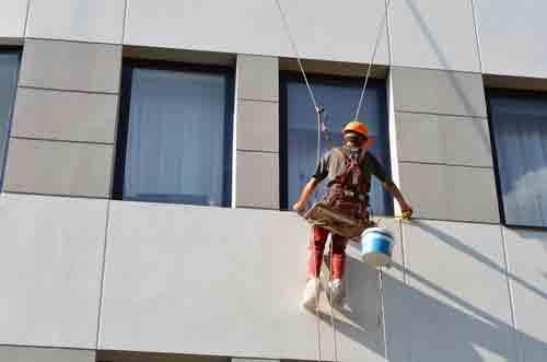 operaio mentre misura la finestra di un edificio