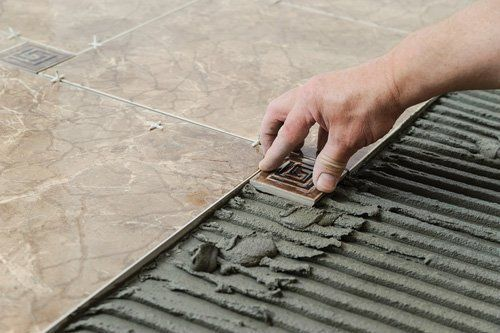 una mano che posiziona una piastrella sul cemento fresco