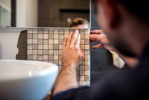 operaio mentre restaura piastrelle di bagno