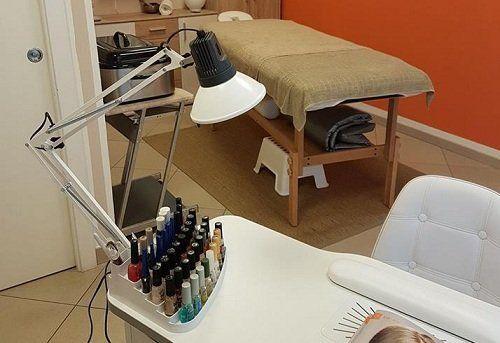 una lampada,degli smalti, una scrivania e un lettino da estetista
