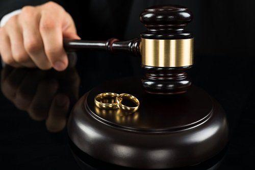 Primo piano della mano di un giudice che regge il martelletto accanto a 2 fedi nuziali