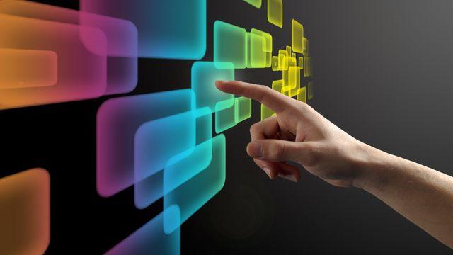Una mano pigia degli schermi astratti su un monitor