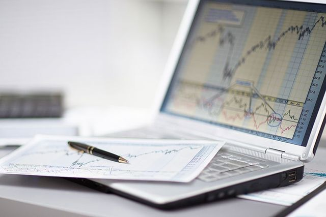 un computer portatile e sopra una penna e un foglio con dei grafici
