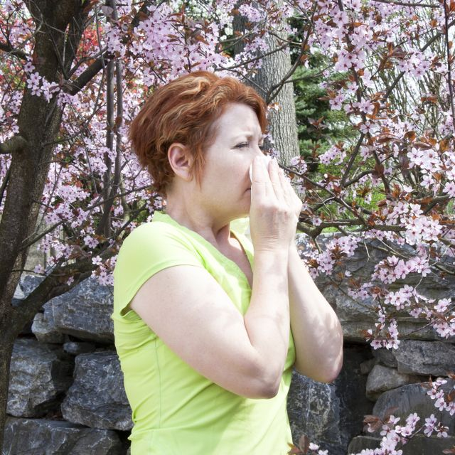 Woman covering her mouth as she sneezes