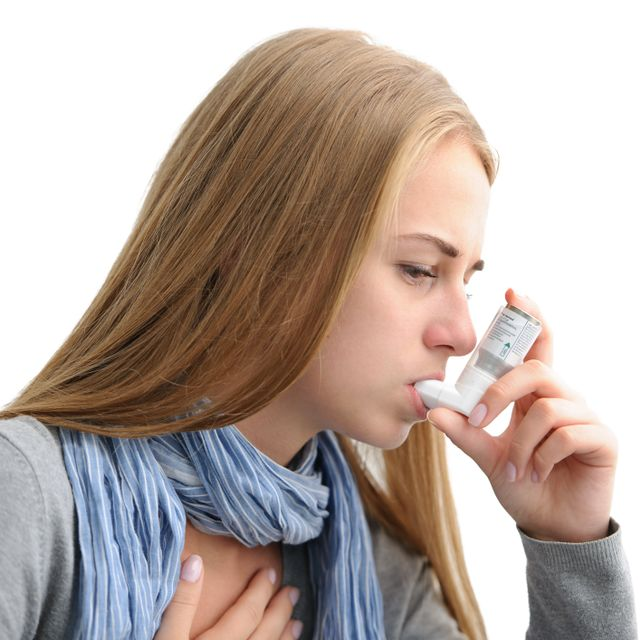 Young woman using an inhaler