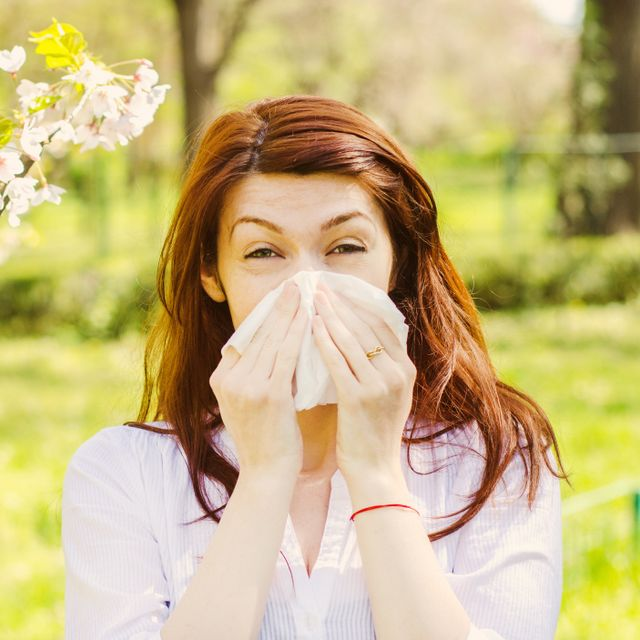 Woman sneezing into tissue paper outdoors