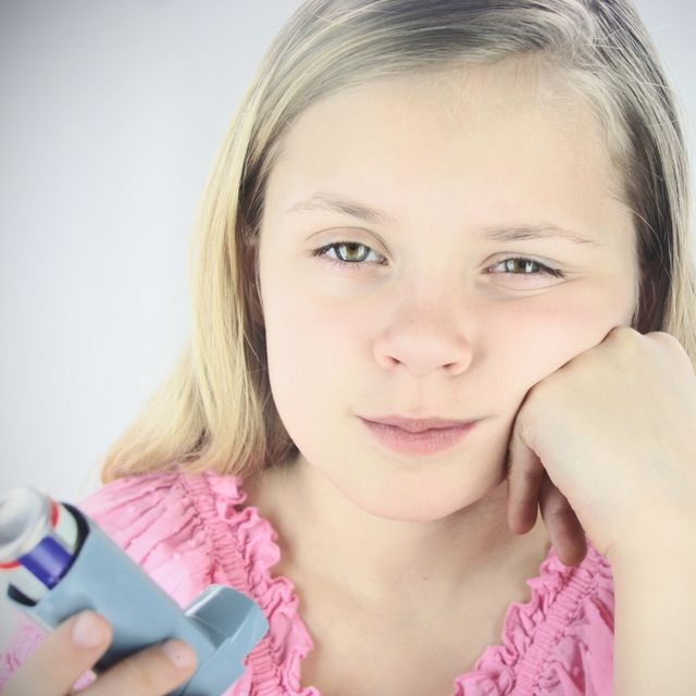 Young girl disappointed in having to use inhaler