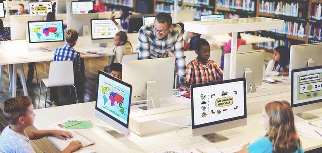 children on computers with teacher