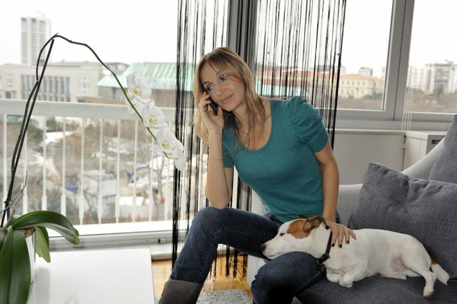 women talking on  phone and sitting next to her dog