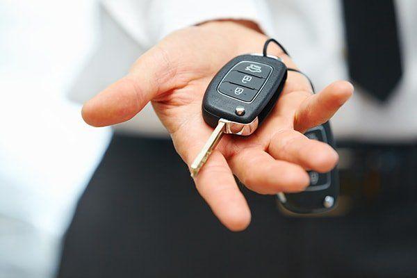 una mano porge le chiavi di un auto