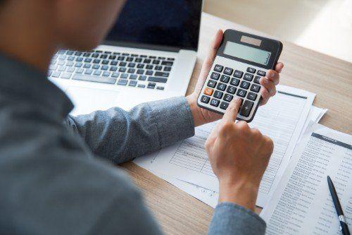 Un uomo di spalle seduto ad una scrivania che usa una calcolatrice