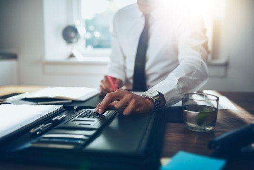 un uomo in cravatta seduto ad una scrivania che usa una calcolatrice