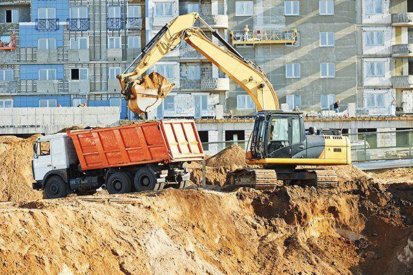 Un escavatore mette della terra nel rimorchio di un camion