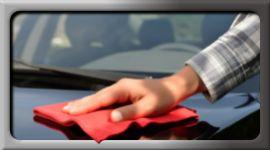 mano di una persona che pulisce con un panno la carrozzeria di un auto