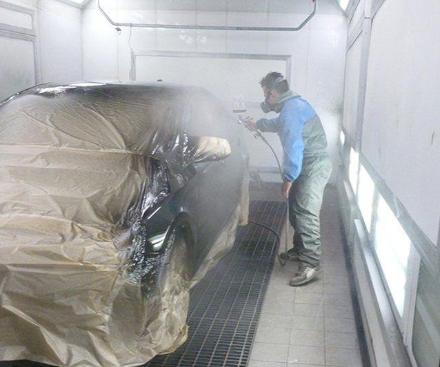 un carrozziere mentre vernicia un'auto nel forno