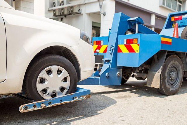 una macchina bianca trainata da un carro attrezzi