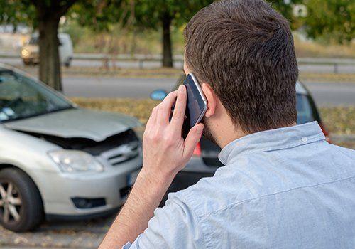 un uomo al telefono e di fronte una macchina incidentata