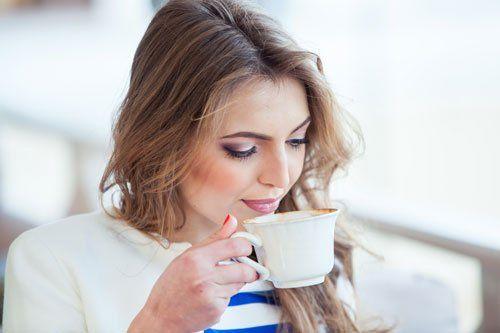 una donna sta bevendo una tazza di caffe'