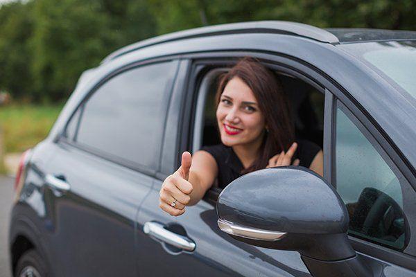una donna in macchina con il pollice in su