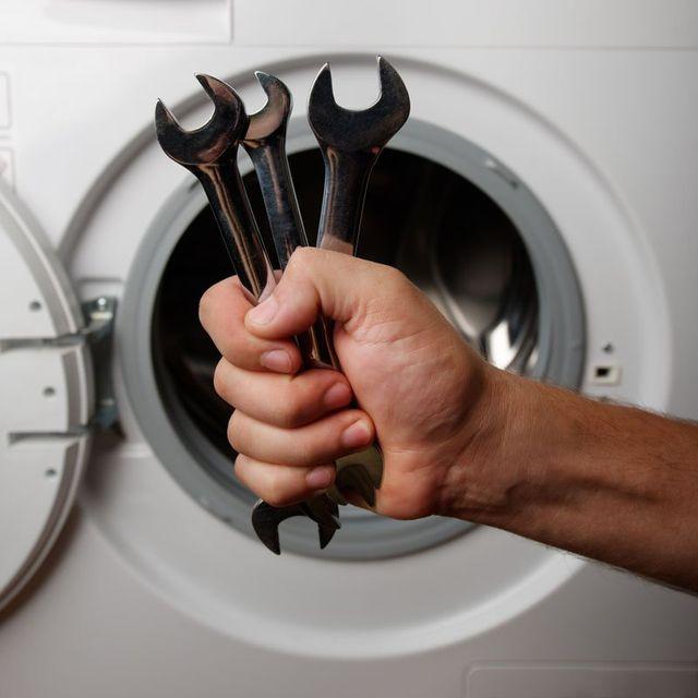 una mano con tre chiavi inglesi e dietro un oblo' di una lavatrice aperto a Abano Terme, PD