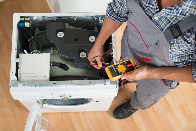 un uomo sta controllando una lavatrice sisassemblata con il tester di correntea Abato Terme, PD