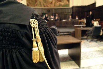 vista di una toga nera di un  giudice con delle corde dorate