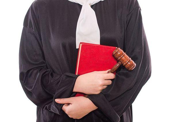 una persona con una toga nera,un bavero bianco e con in mano un libro e un martello
